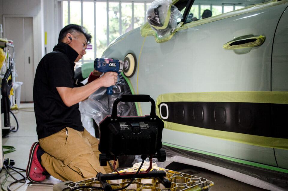 CITROEN NEW C3のボディを小型LEDライトを当てながら研磨するスタッフ