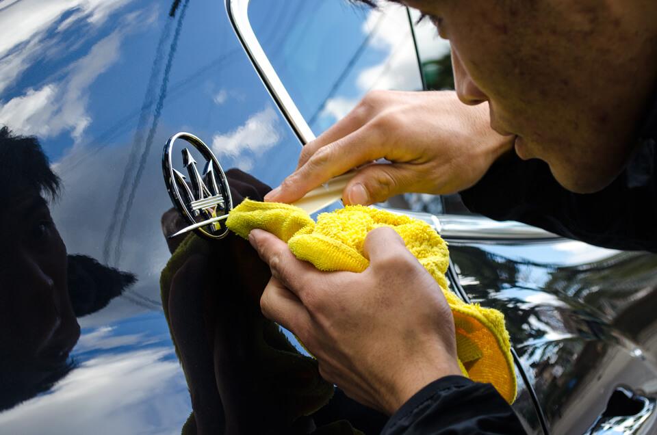 微細な汚れも逃さないように、Maserati levanteのエンブレムの最終仕上げをしているCARHEART神戸のスタッフ