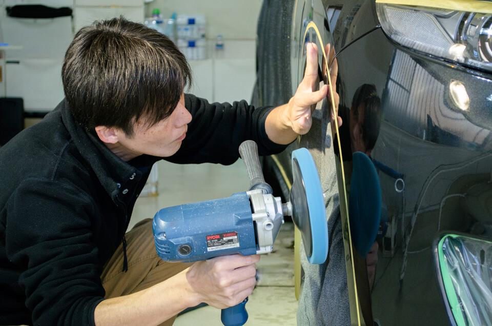 Maserati levanteへGENESISコーティングの下地処理をしている時に塗装の状態を確認するCARHEART神戸のスタッフ