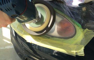 平成12年式のMAZDAのロードスターの曇ったヘッドライトをポリッシャーで磨いているところ