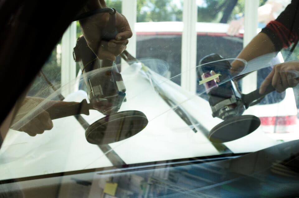 日産セレナフロントガラス研磨を施工しているところ。熟練した2人のスタッフが同時に磨いている。