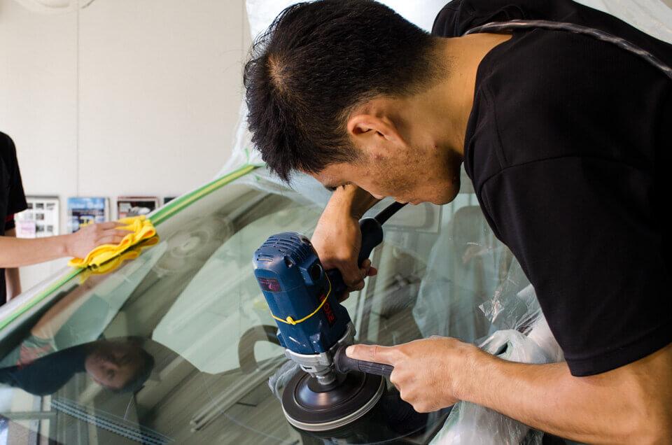 日産セレナにフロントガラス研磨を施工するスタッフ。