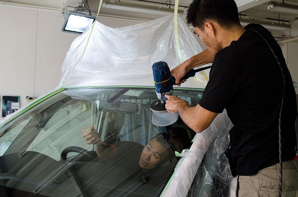 日産セレナにフロントガラス研磨を施工するスタッフと内側からキズの位置を確認するスタッフ