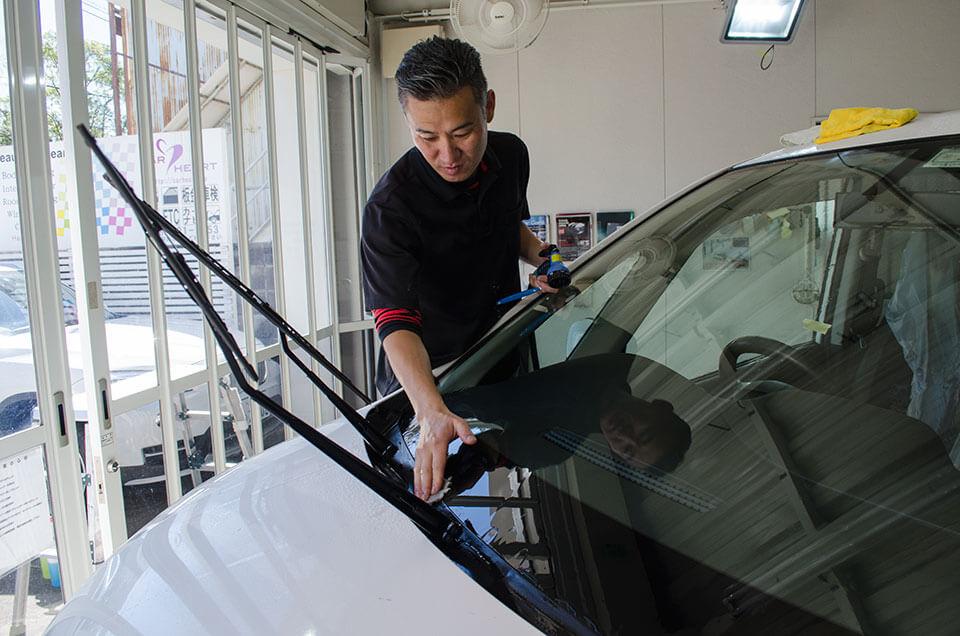 日産セレナにフロントガラス研磨をし終えたあとに、汚れを除去するスタッフ