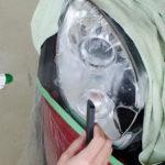 CARHEART神戸のスタッフがMINIのヘッドライトにプロテクションフィルムを施工しようとしているところ