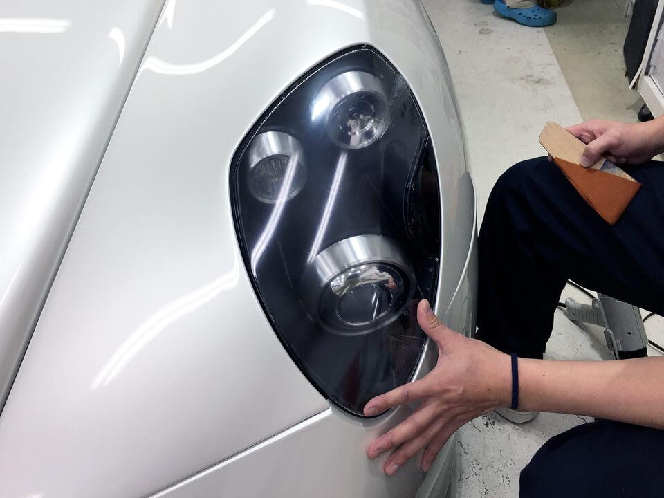 AlfaRomeo 8C Spiderのヘッドライトにプロテクションフィルムを貼っているところ