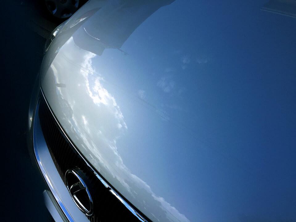 LEXUS GSにGENESISコーティング、ホイールコーティング、ヘッドライトクリア塗装を施したあとのボンネット。爽やかに青空が写り込んでいる。