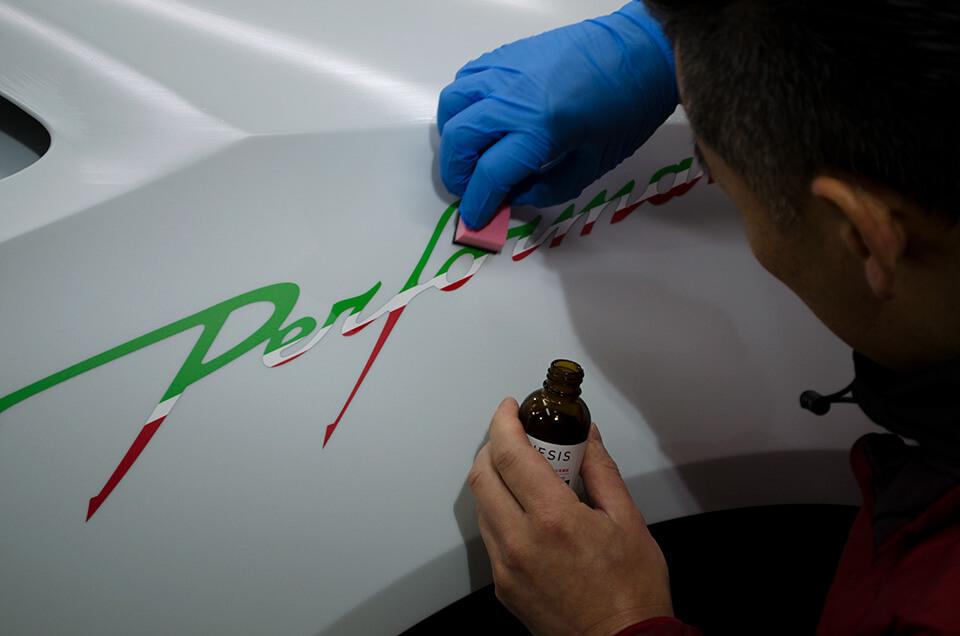 Lamborghini HURACÁN PERFORMANTEに貼り付けたPerformanteステッカーにGENESISガラスコーティングを施工しているところ
