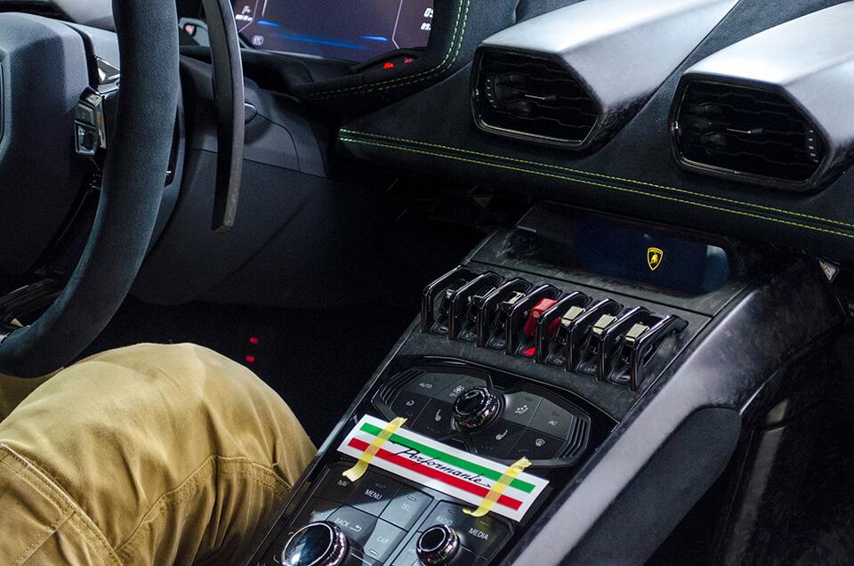 Lamborghini HURACÁN PERFORMANTE ランボルギーニ ウラカン ペルフォルマンテ のセンターコンソールに特注ステッカーを貼り付けるところ