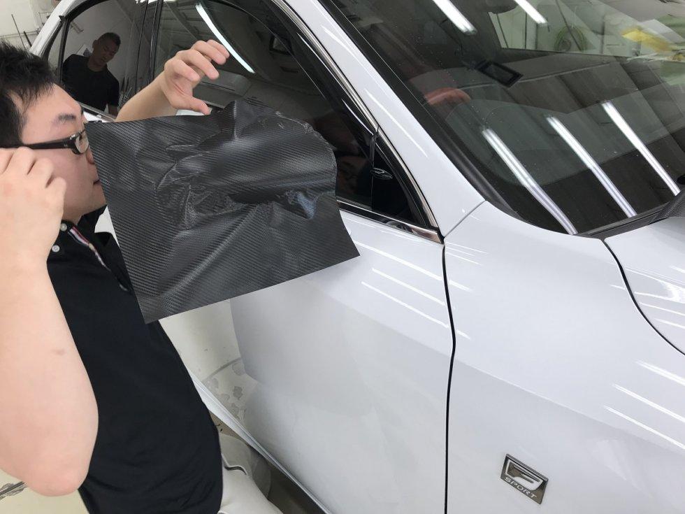LEXUS ISのサイドミラーにカーボンシートを貼り付けているところ