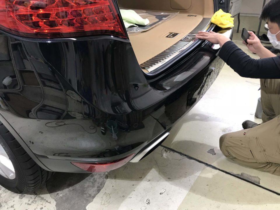 Porsche Cayenneのリアドアバンパーにプロテクションフィルムを貼り付けしているところ