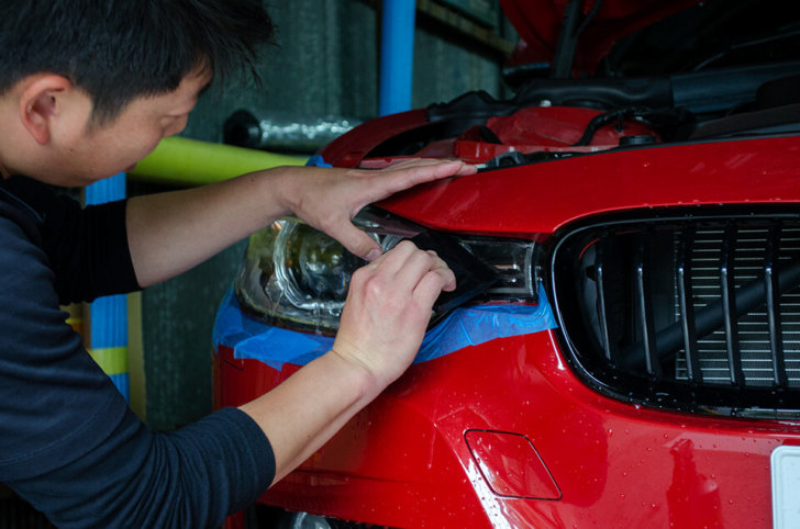 BMW 320i F30のヘッドライトにUVカット93%のプロテクションフィルムを施工しているところ