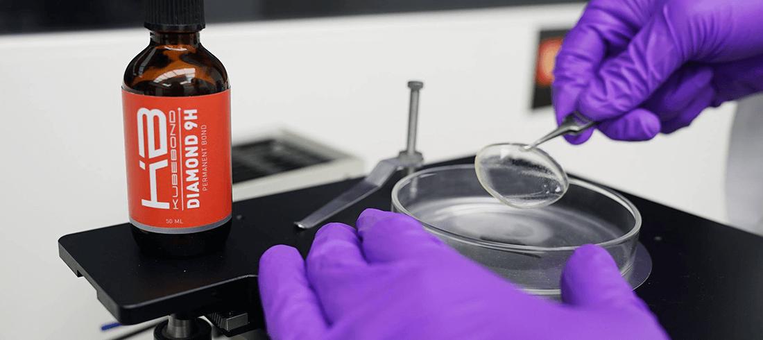液体から固形化したKUBEBOND DIAMOND9Hナノセラミックコーティングのフィルムを持つCHOOSE NanoTechの研究員