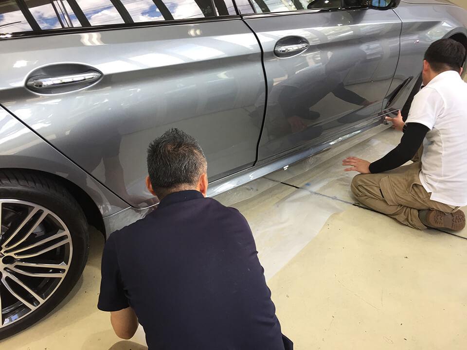 BMW G30のロッカーパネルにプロテクションフィルムを施工しているところ
