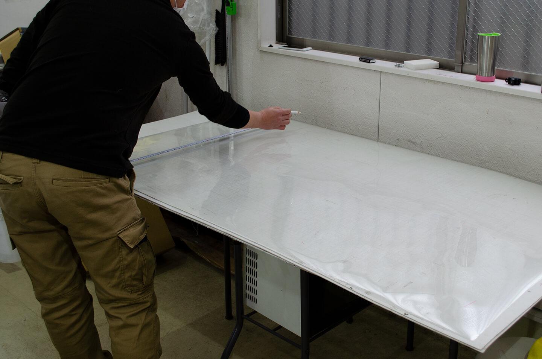 フロントガラスに施工するために透明断熱フィルムを出しているところ