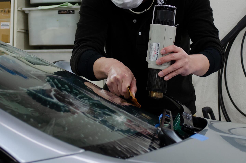 ASTON MARTIN V8 Vantage N430のフロントガラスに透明断熱フィルムを施工しているところ