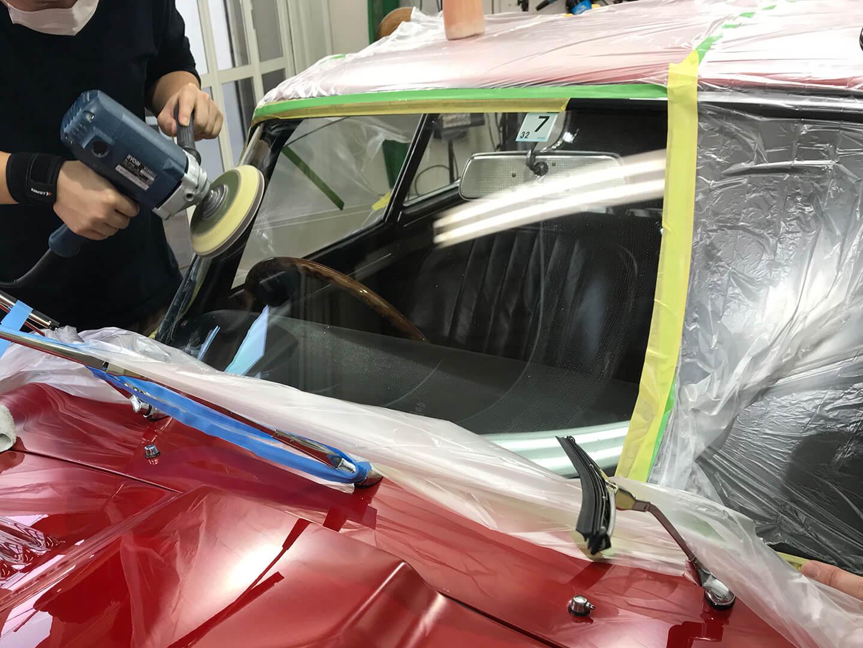 ジャガー Eタイプのフロントガラスを磨いているところ