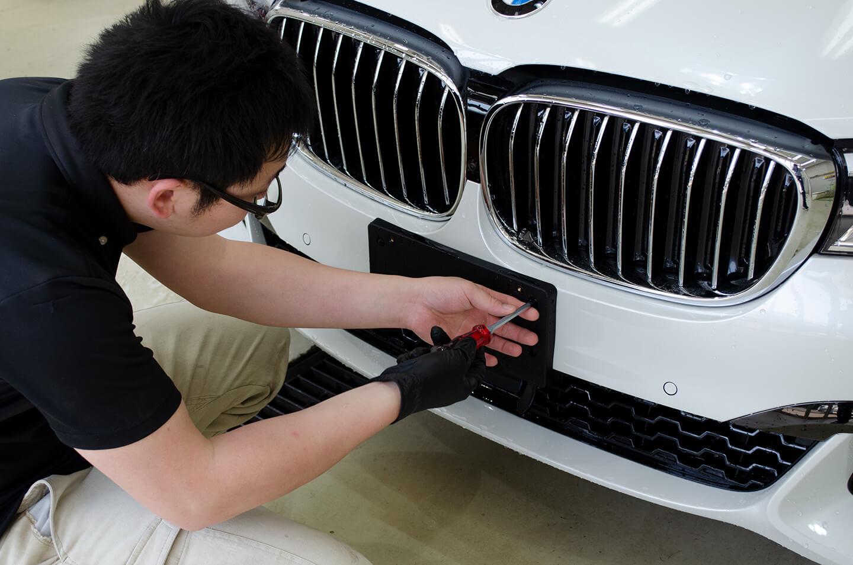BMW G11 750iのナンバーベースを外しているところ