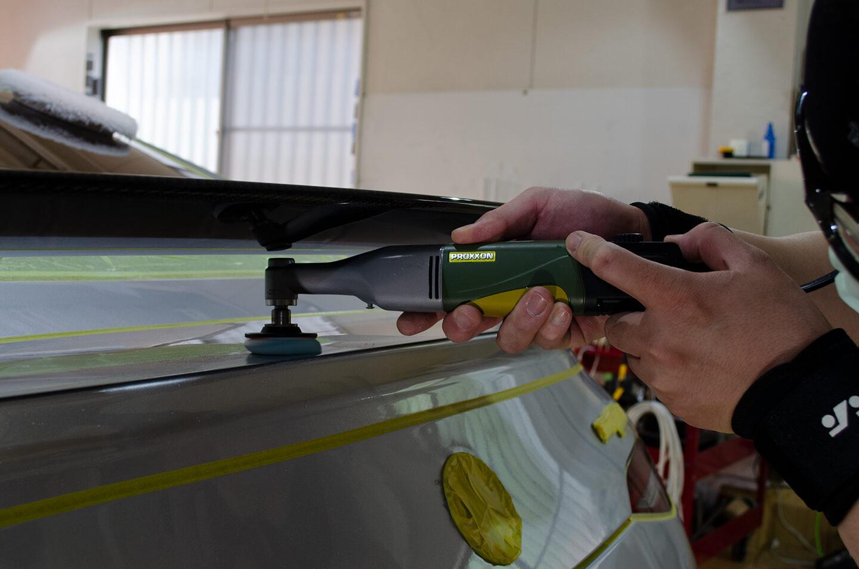 AMG GT 63Sのリアウィング下をミニポリッシャーで磨いているところ