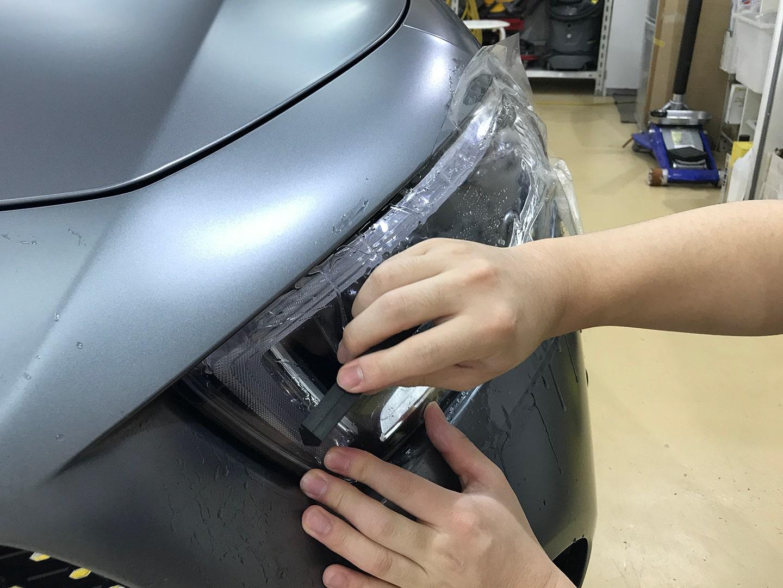 プロテクションフィルムをメルセデス CLS450のヘッドライトに施工しているところ