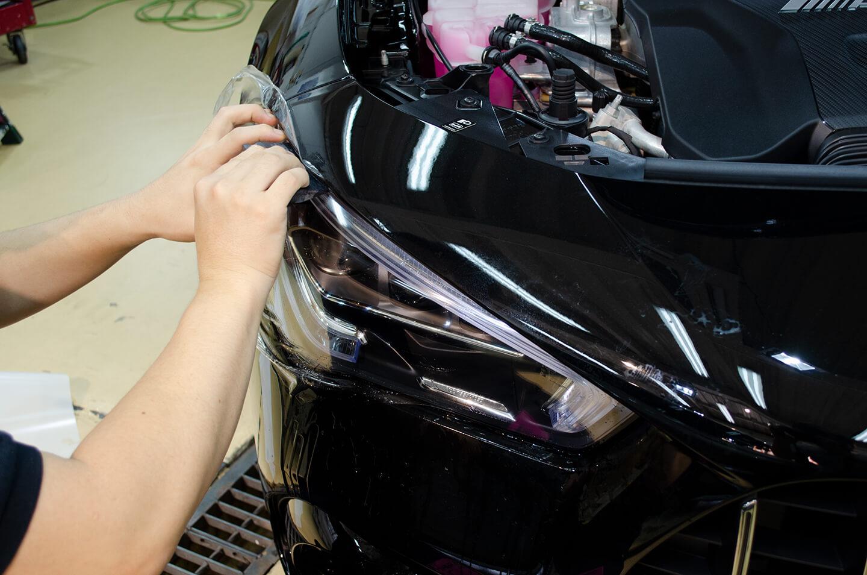 メルセデス AMG CLA 45Sのヘッドライトにプロテクションフィルムを施工しているところ