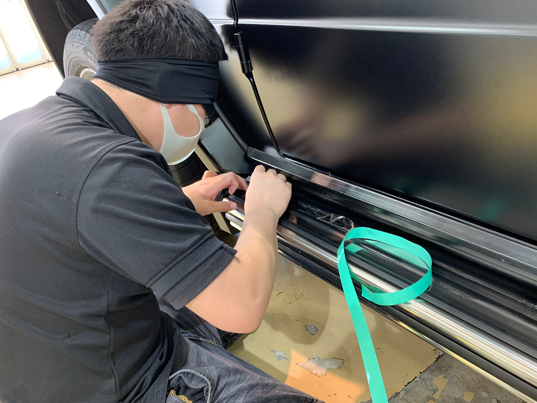 メルセデス AMG G63 マットブラックのサイドステップにプロテクションフィルムを施工しているところ
