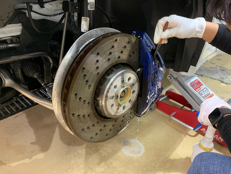 BMW X4M Competitionのブレーキキャリパーをクリーニングしているところ