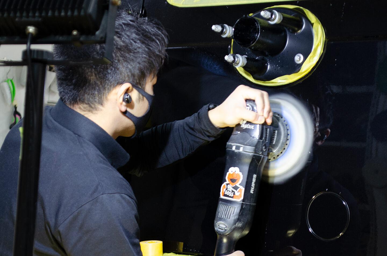 メルセデス・ベンツ G350d オブシディアンブラックのタイヤカバー裏を研磨しているところ